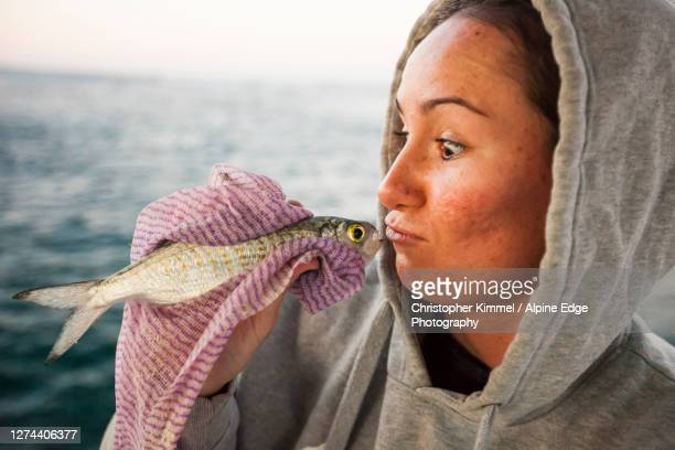 young woman pretending to kiss caught fish, perth, western australia, australia - only young women stock pictures, royalty-free photos & images
