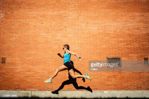 young woman professional athlete running outdoors - miljko stock pictures, royalty-free photos & images