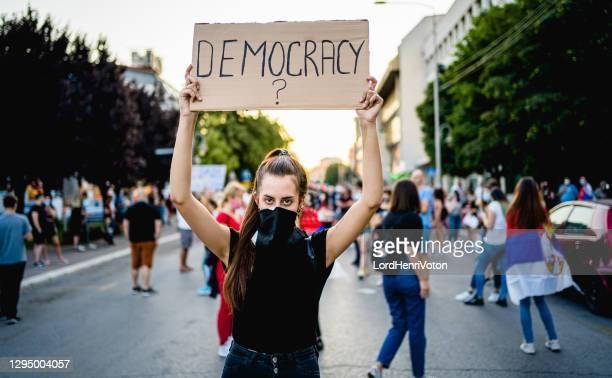 """junge demonstrantin hält plakat mit dem text """"demokratie?"""" - demokratie stock-fotos und bilder"""