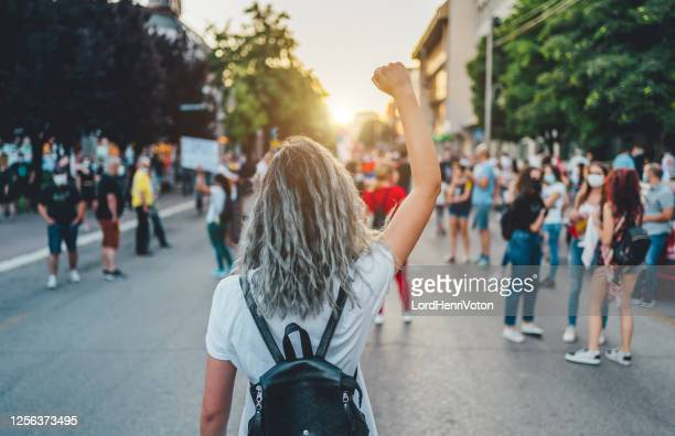young woman protester raising her fist up - protestor stock pictures, royalty-free photos & images