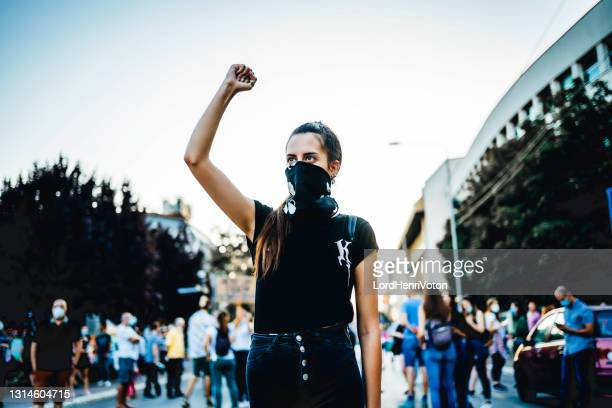 young woman protester raising her fist up - black lives matter stock pictures, royalty-free photos & images