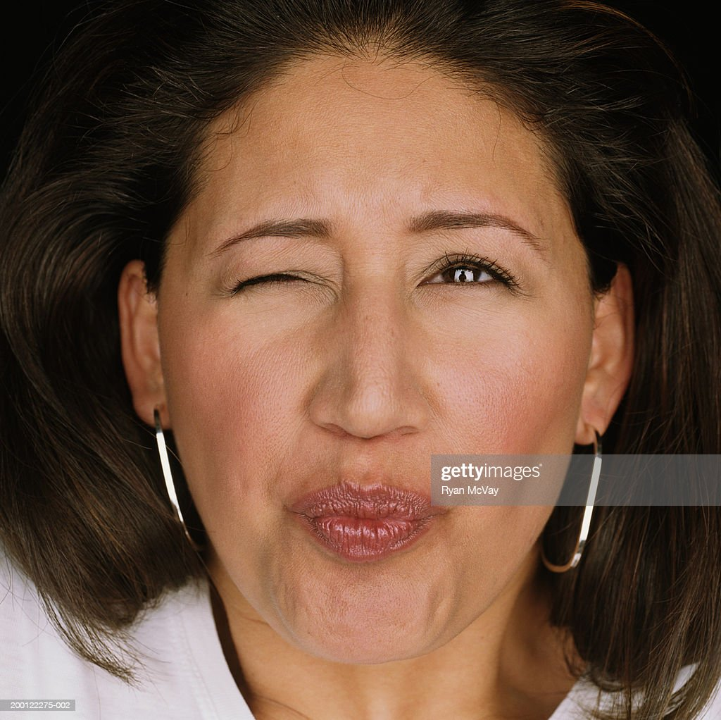 Young woman puckering lips and shutting one eye, portrait, close-up : Stock Photo