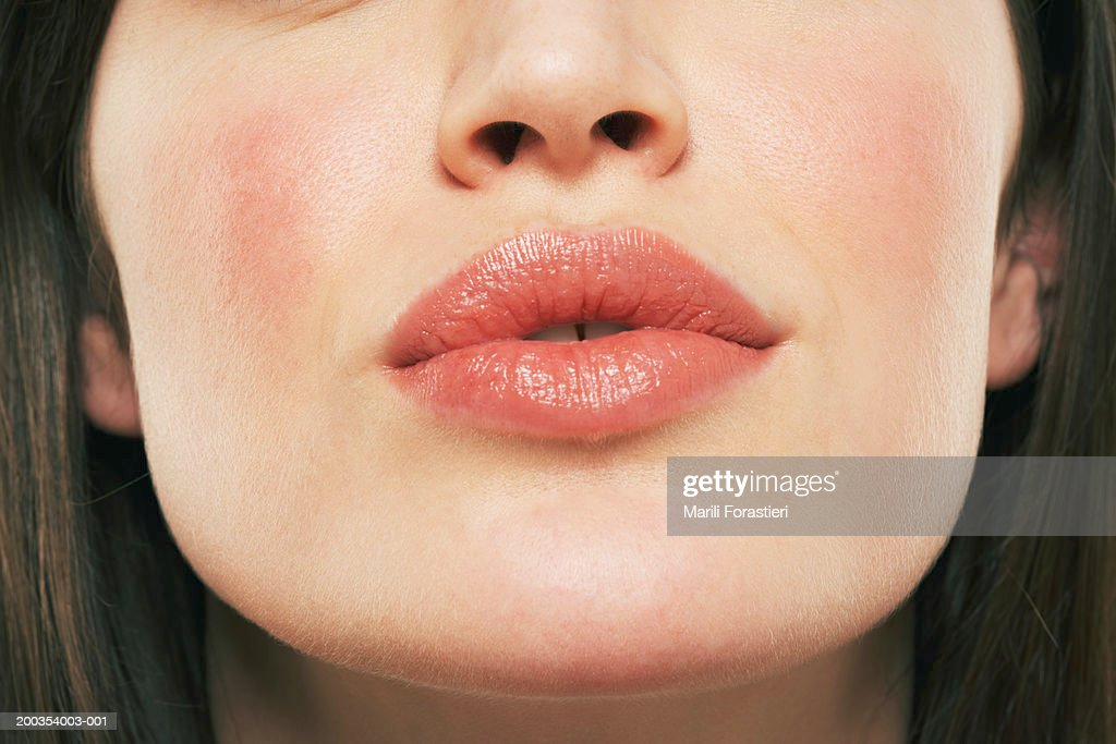 Young woman puckering lips, close-up : Stock Photo