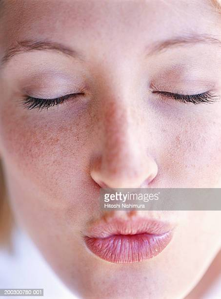 Young woman puckering lips, eyes closed, close-up