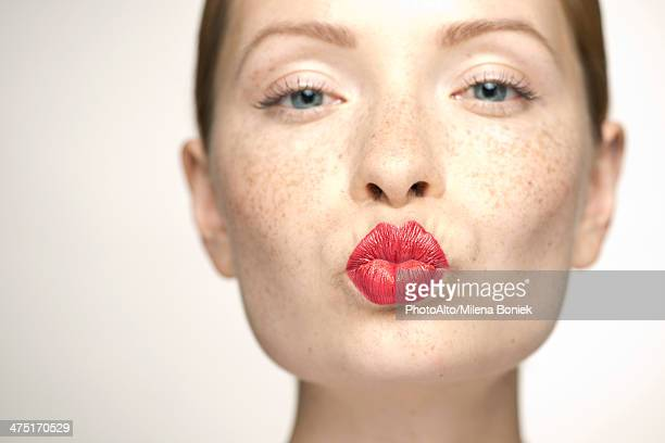 young woman puckering lips, portrait - lippenstift stock-fotos und bilder