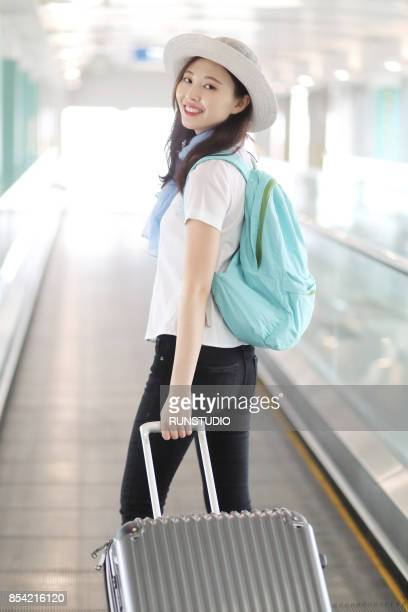 young woman pulling bag along walkway, rear view - travolator stock pictures, royalty-free photos & images
