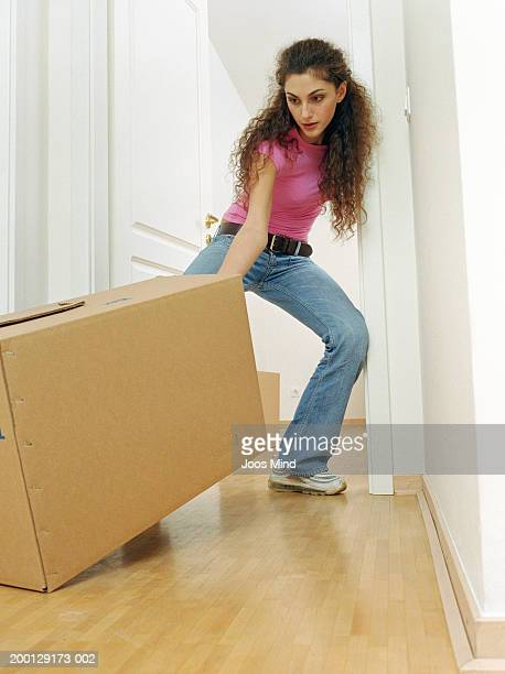 young woman pulling box towards doorway - dragging stock pictures, royalty-free photos & images