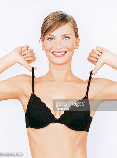 young woman pulling bra straps, smiling, portrait - bras stock pictures, royalty-free photos & images