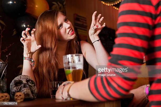 Young woman pulling rostros en sus amigos en el bar
