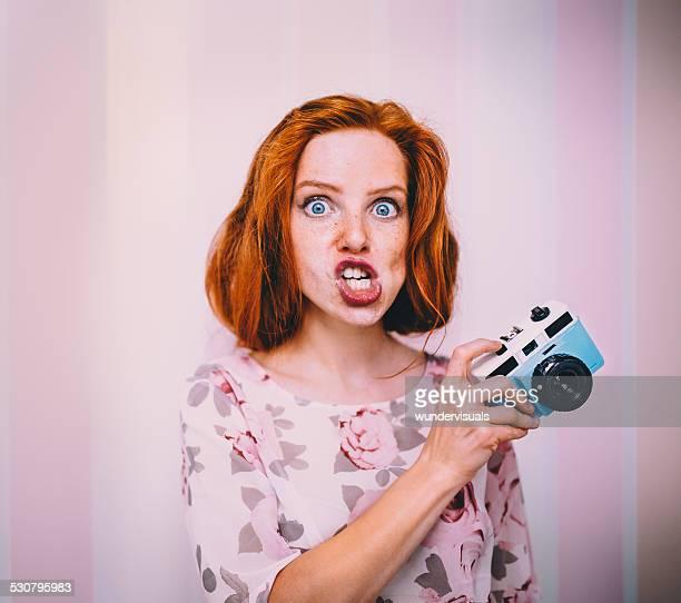 giovane donna tirando facce con macchina fotografica in mano - fare le boccacce foto e immagini stock