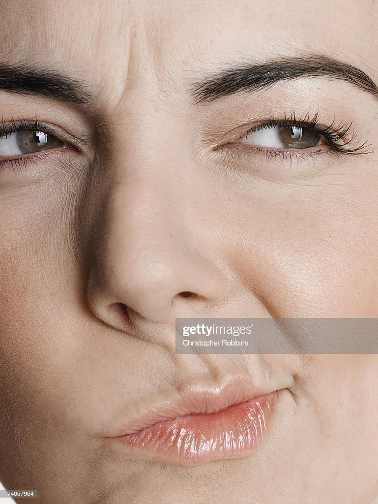 Young woman pulling facial expression, close-up of face : Stock Photo