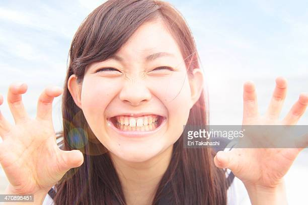 Young woman pulling funny face and hands like claws