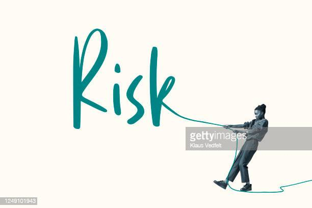young woman pulling green rope forming word risk - casual clothing imagens e fotografias de stock