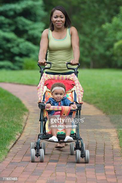 young woman pulling her daughter in a baby stroller - baby stroller stock pictures, royalty-free photos & images