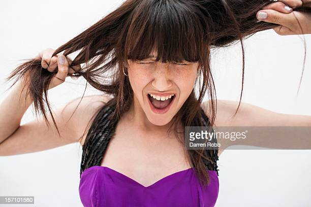 Young woman pulling her hair, shouting