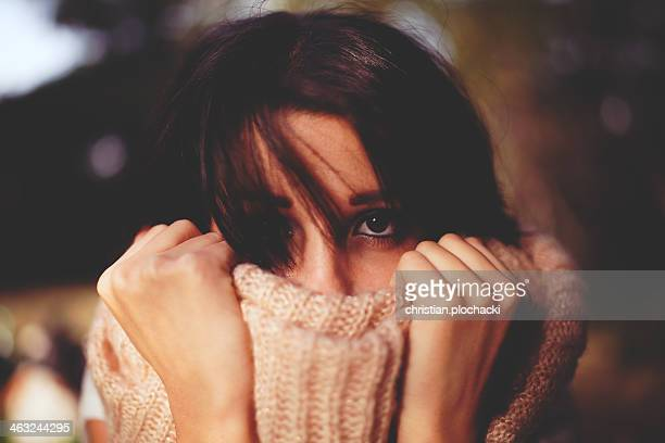 Young woman pulling her muffler into her face