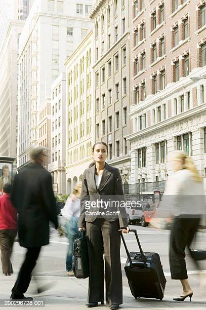 young woman pulling luggage down urban sidewalk (blurred motion) - schiff stock photos and pictures