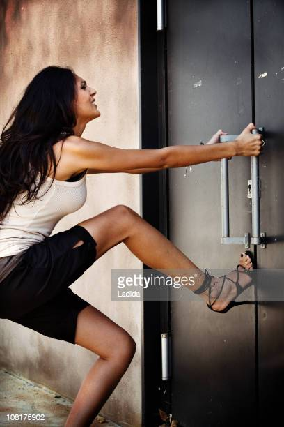 Young Woman Pulling on Door