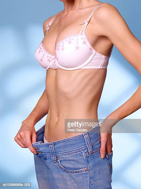young woman pulling on waist of jeans, close-up - anorexia nervosa stock pictures, royalty-free photos & images