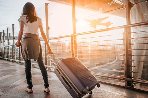 Young woman pulling suitcase in  airport terminal. Copy space 1173736603