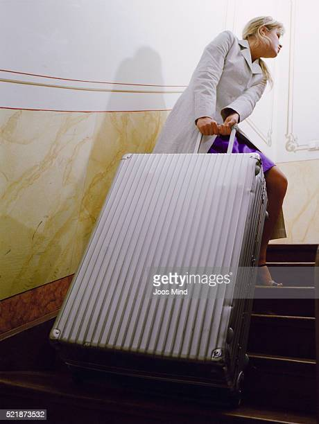 Young Woman Pulling Suitcase up Stairs