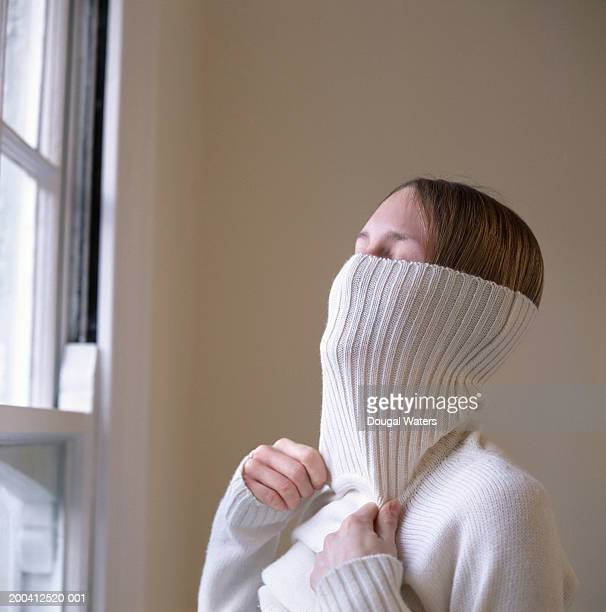 Young woman pulling turtleneck jumper over head, close up