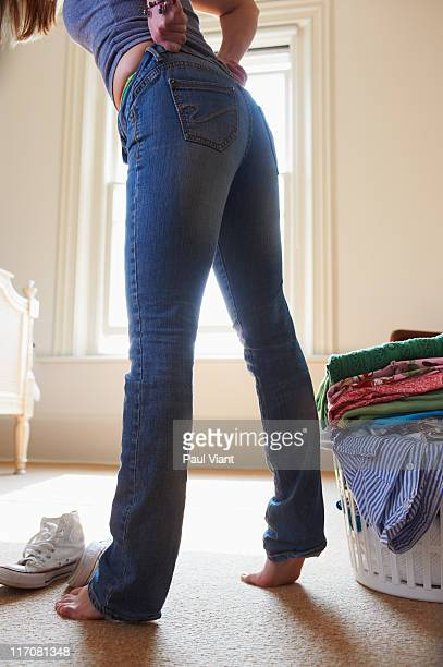 young woman pulling up tight jeans