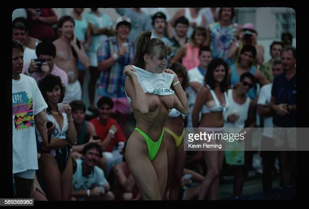 A young woman pulls up her tank top to expose her tanned breasts at a Spring Break party in Fort Lauderdale Florida