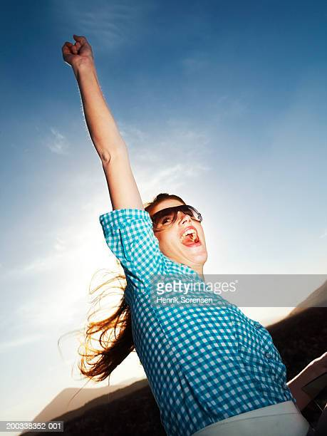 Young woman punching air, cheering, outdoors, low angle view