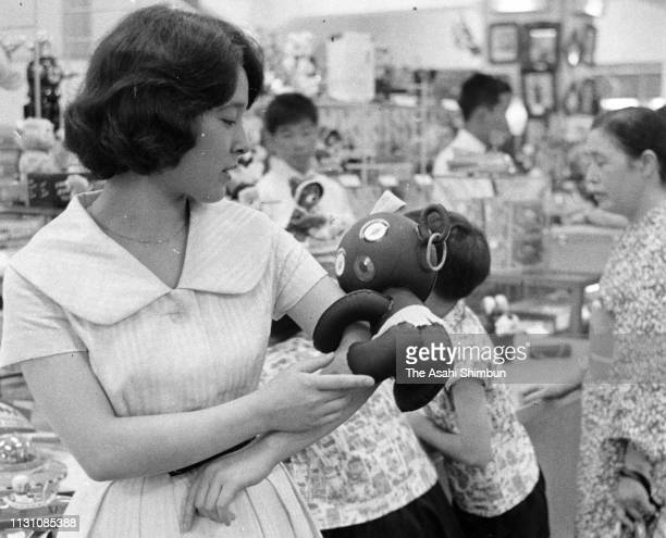 A young woman purchases a DakkoChan doll on July 29 1960 in Tokyo Japan