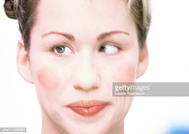 young woman pursing lips and crossing eyes, wearing make up, close-up, blurred - ugly lips stock photos and pictures