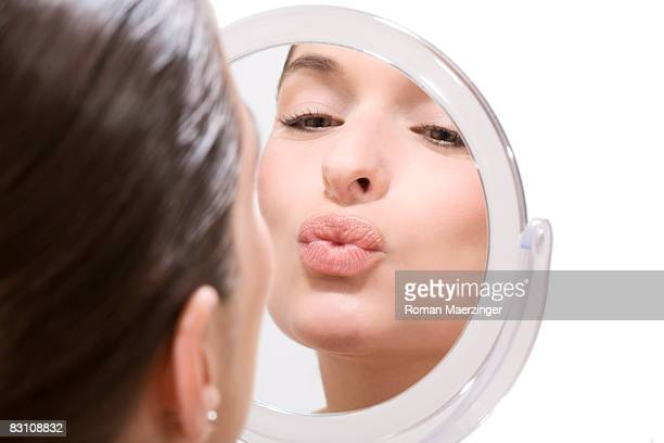 Young woman looking at mirror, pouting, close-up