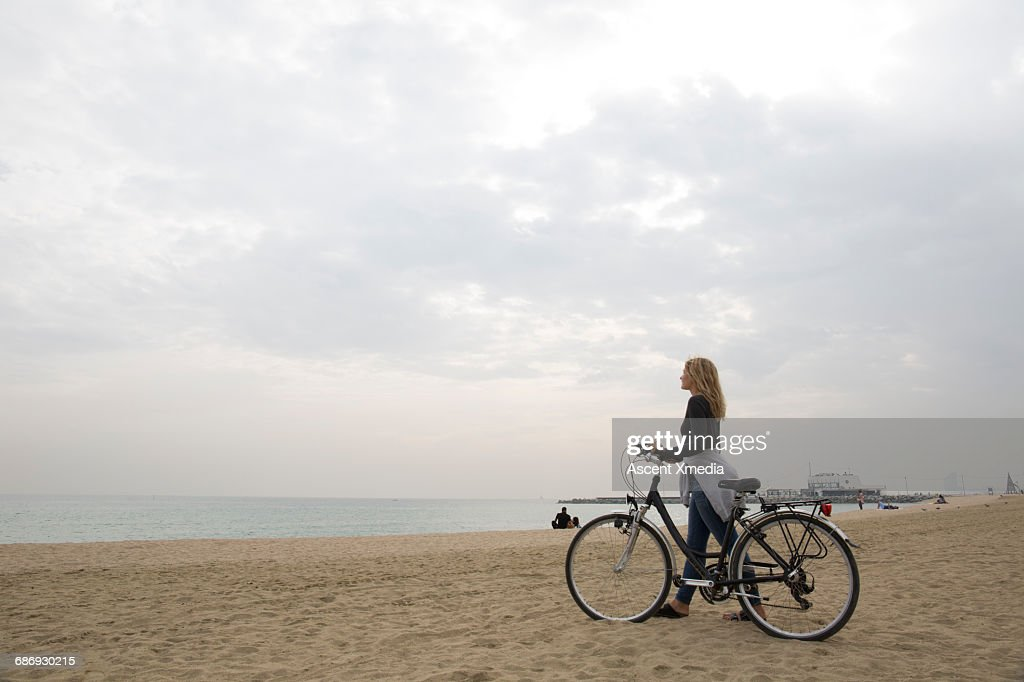 Young woman pushes bike along beach, to sea : Stock Photo
