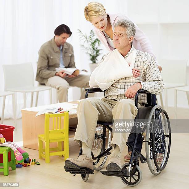 young woman pushing a mature man in a wheelchair