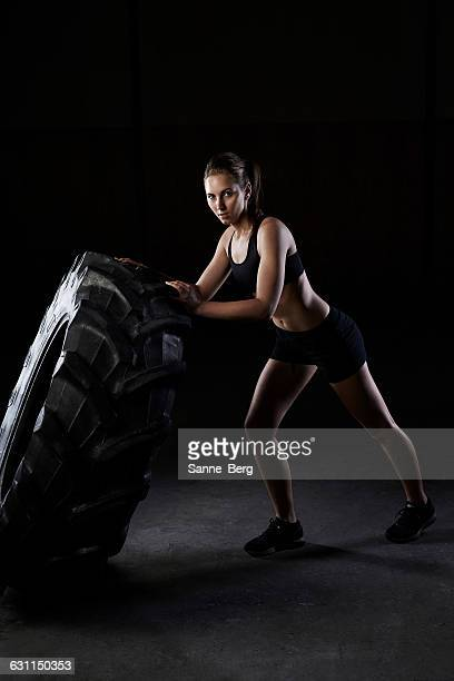 Young woman pushing a truck tire in the gym