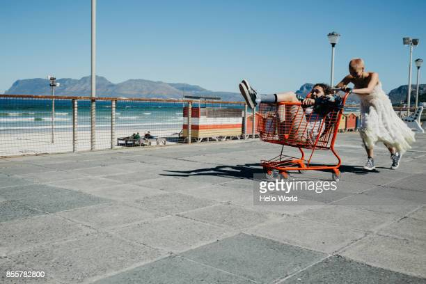 young woman pushing a young man in trolley - ondeugendheid stockfoto's en -beelden