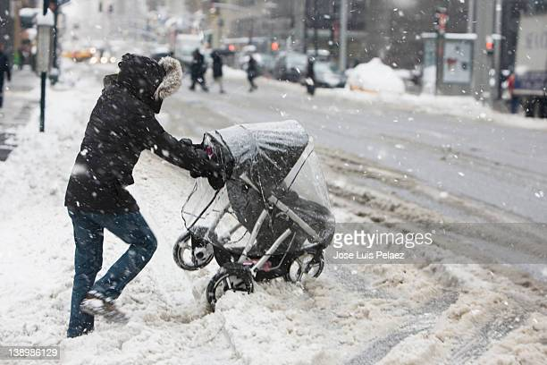 young woman pushing baby stroller through wet snow - three wheeled pushchair stock pictures, royalty-free photos & images