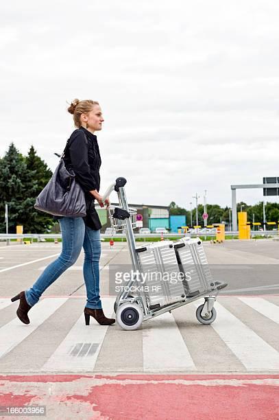 Young woman pushing baggage cart on crosswalk