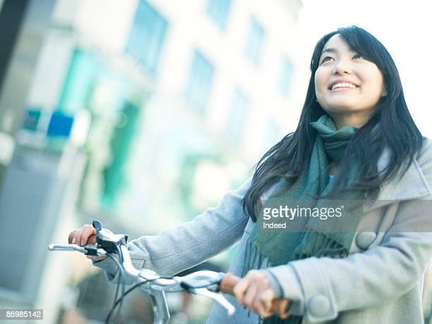 Young woman pushing bicycle and walking, smiling