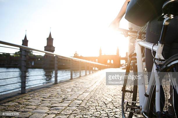 Young woman pushing bicycle by river