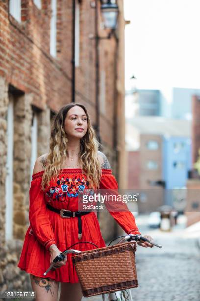 young woman pushing bicycle down city street - two tone color stock pictures, royalty-free photos & images