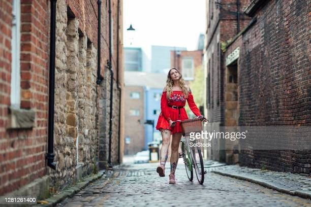 young woman pushing bicycle down cobbled street - two tone color stock pictures, royalty-free photos & images