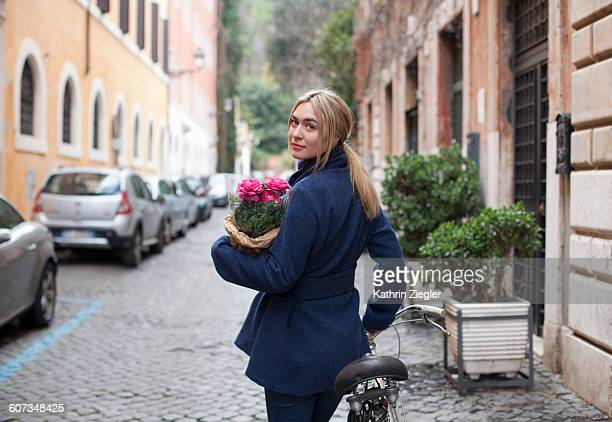 young woman pushing bicycle on Roman cobbled road