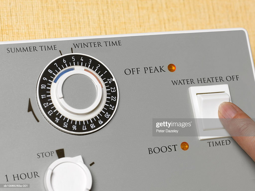 Young woman pushing bottom on water heater control : Foto stock