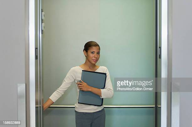 Young woman pushing button in elevator