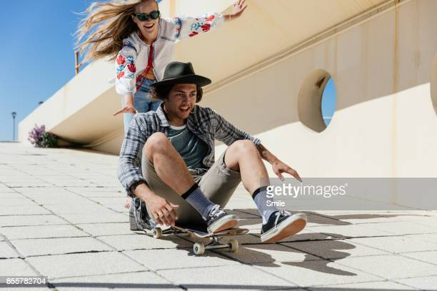 young woman pushing man sitting on skateboard - generation z stock-fotos und bilder