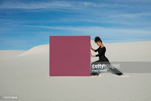 young woman pushing maroon portal on white sand dunes at desert - sforzo foto e immagini stock
