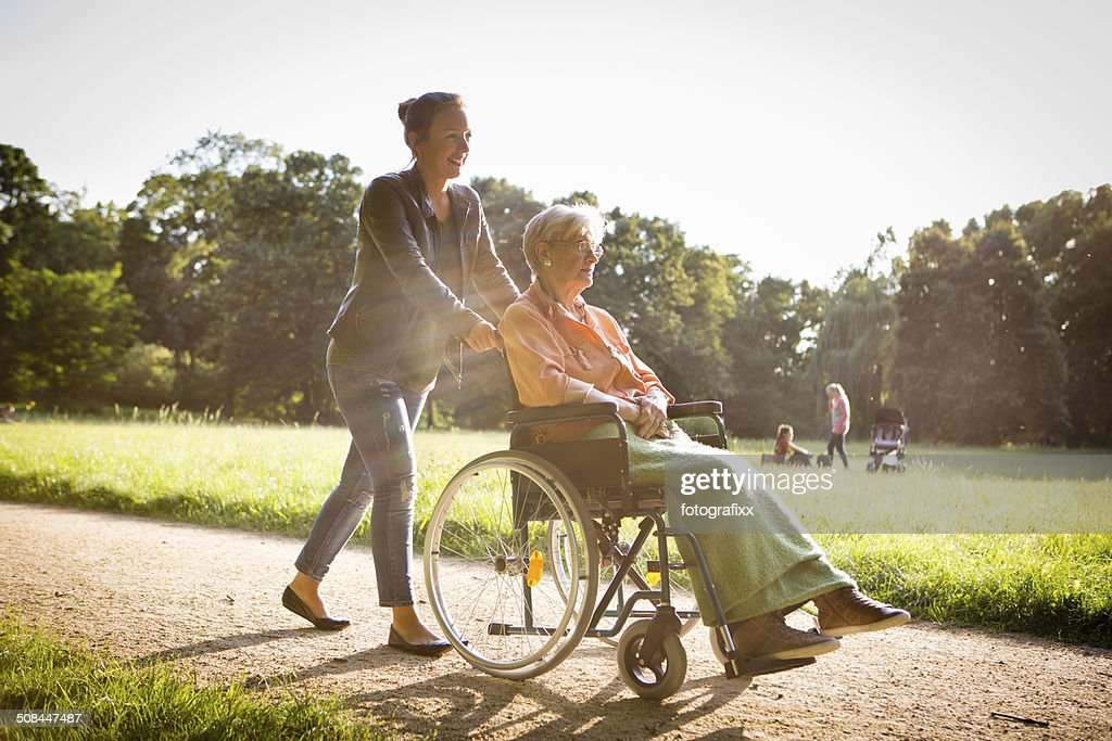 young woman pushing senior lady in wheelchair through a park : Stock Photo