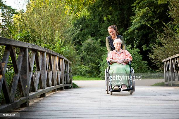 young woman pushing senior lady in wheelchair through a park - simple living stock pictures, royalty-free photos & images