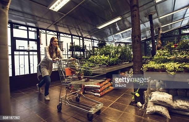 Young woman pushing shopping cart in a garden house.